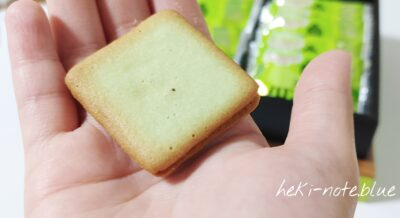 海老名メロンパン風味のラングドシャの個装を開封して中身を出している写真。中身だけでなく外側もメロンのような色